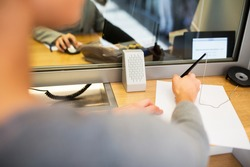 people and finance concept - customer with pen and paper writing application at bank office