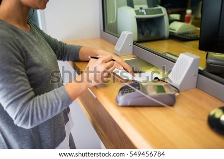 people and finance concept - customer with pen and paper writing application at bank office #549456784