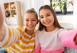 people and friendship concept - happy smiling teenage girls taking selfie at home
