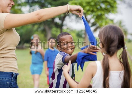 People and fun, group of male and female school kids with young woman working as educator playing game outdoor at summer camp