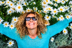 People and happiness concept lifestyle with happu and cheerful adult beautiful caucasian young woman smile with green and coloured daisies background - leisure activity and park outdoor