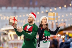 people and holidays concept - happy couple in santa hats and ugly sweaters with gifts over christmas market background