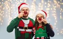 people and holidays concept - portrait of happy couple in santa hats making noses of red christmas balls at ugly sweater party over festive lights background