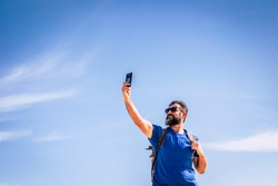People and internet technology man with beard and sunlgasses loooking for signal with a mobile phone device - people traveling with backpack for adventure concept and alternative vacation - blue sky
