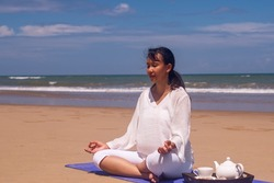 people and leisure concept- back view of woman meditating and drinking tea on the tropical beach with blue sky vackground.