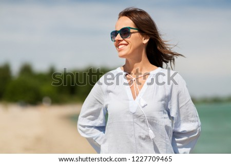 people and leisure concept - happy smiling woman in sunglasses on summer beach #1227709465