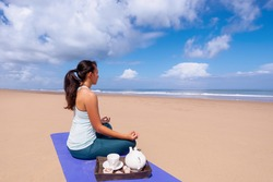people and leisure concept- young asian woman meditating and drinking tea on the tropical beach