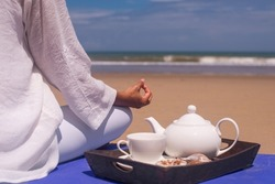 people and leisure concept- young asian woman meditating and drinking tea on the tropical beach.