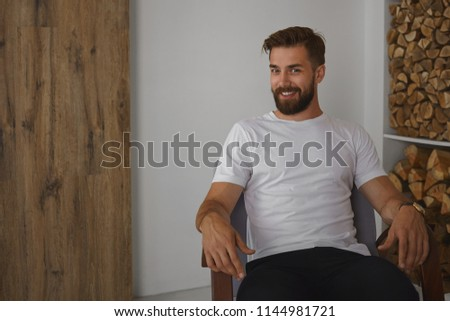 People and lifestyle concept. Indoor portrait of friendly looking young businessman with trendy hairstyle and trimmed fuzzy beard relaxing at home, sitting in armchair and smiling joyfully