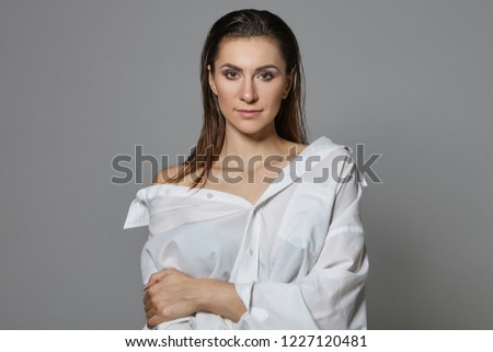 People and lifestyle concept. Picture of sensual sexy gorgeous female with wet loose hair and bright make up staring at camera with smile, wearing stylish white shirt with one naked shoulder