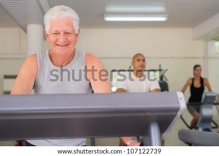 People and sports, elderly man working out on treadmill in fitness gym among young people