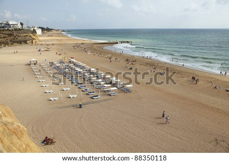 People and sun beds on the wide beach of Albufeira in Portugal