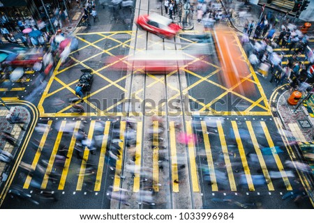 People and taxi cabs crossing a very busy crossroads in the central district, Hong Kong, China