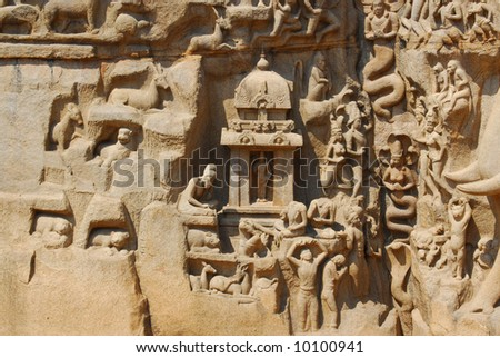 people and temple carved in stone wall hindu temple mahabalipuram, india