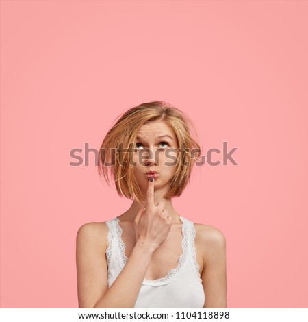 People and thoughts concept. Attractive Caucasian woman looks pensively upwards, keeps fore finger near round lips, wears sleepwear, plans day, has something in mind, isolated on pink studio wall