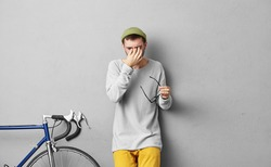 People and tiredness concept. Young attractive male with thick beard, dressed in fashionable clothes, taking off his glasses and scratching eyes, being tired after long journey by bicycle alone