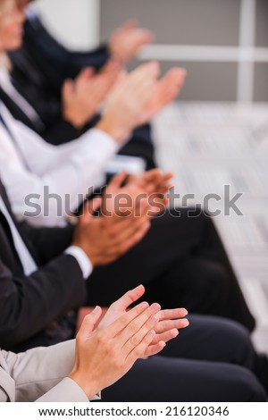 People applauding. Group of business people clapping hand while sitting in a row