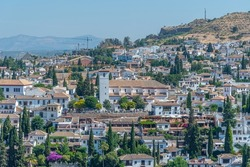 People are admiring Alhambra from viewpoint of San Nicolas in Granada, Spain