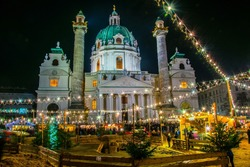 People are buying various articles, admire small enclosure with goats and sheep and play with hay during a christmas market taking place in front of the karlskirche in vienna