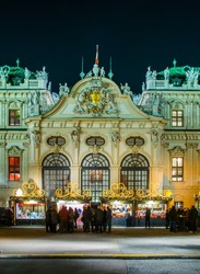 People are buying various articles during a christmas market during night taking place in front of the belvedere palace in vienna.
