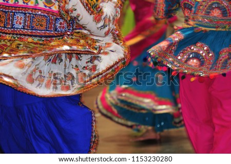 People are dancing wearing vibrant costume during nine day garba and dandiya dance Navratri festival. It is a Hindu festival dedicated to the worship of Goddess celebrated by Indian across the world.