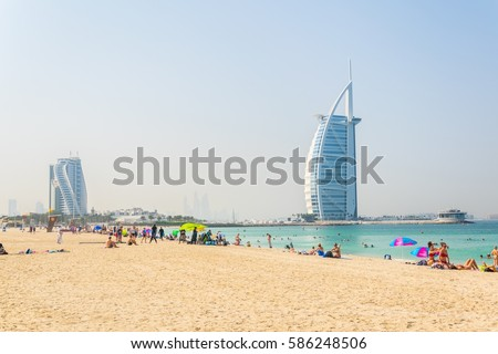 People are enjoying a sunny day on a beach in front of the Burj al Arab hotel in Dubai, UAE