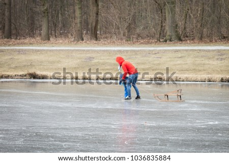 People are ice skating on the frozen lake in the city The Hague (Den Haag)  trees in the background. Schaatsen in het Haagse Bos.