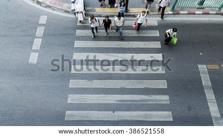 People are moving across the crosswalk on the city road (on top view) #386521558