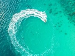 People are playing a jet ski in the sea.Aerial view. Top view.amazing nature background.The color of the water and beautifully bright. Fresh freedom. Adventure day.clear turquoise at tropical beach