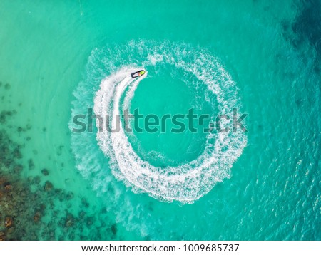 People are playing a jet ski in the sea.Aerial view. Top view.amazing nature background.The color of the water and beautifully bright. Fresh freedom. Adventure day.clear turquoise at tropical beach. #1009685737