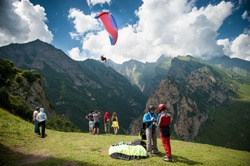 people are preparing for flight on a paraglider on a background of mountains, clouds and flying paraglider