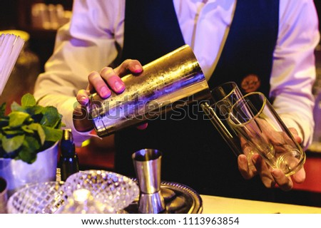 people are resting at a banquet. the barman pours drinks - Shutterstock ID 1113963854