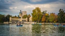 People are rowing boats on the lake in Buen Retiro park during fall / autumn at sunset with colorful foliage in the background in Madrid, Spain.