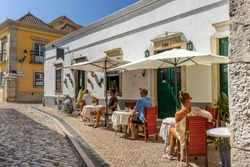 People are sitting at the outside terrace of a small cafe in the historic centre of Faro, Portugal.