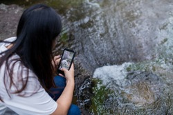 People are using phones to take pictures of waterfalls.