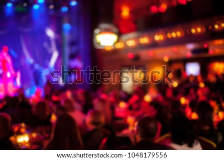 People are watching a concert of classical / jazz / blues music. blurred young and adult women and men and other people who are watching while listening to a concert of pop music in a concert hall #1048179556