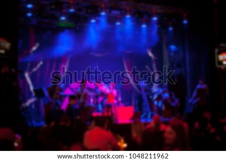 People are watching a concert of classical / jazz / blues music. blurred young and adult women and men and other people who are watching while listening to a concert of pop music in a concert hall #1048211962