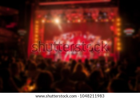 People are watching a concert of classical / jazz / blues music. blurred young and adult women and men and other people who are watching while listening to a concert of pop music in a concert hall #1048211983