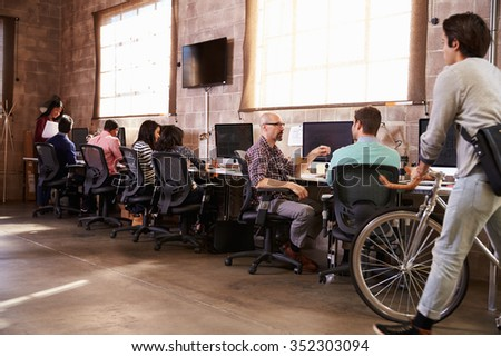 People Arriving For Work In Modern Design Office