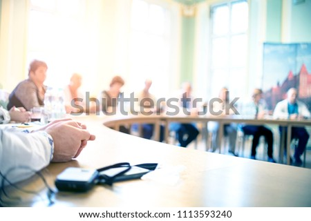 People at a round table discuss different issues. Focus on hand