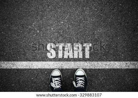People at a starting line with start text on floor