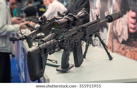 People at the counter with samples of automatic weapons