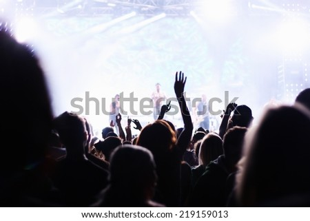 People attending pop concert, silhouettes of crowd dancing in front of stage, shallow DOF