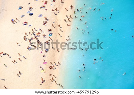 People bathing in the sun, swiming and playing games on the beach. Tourists on the sand beach of Navagio Zakynthos Greece. #459791296