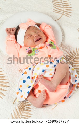 People, beautiful newborn baby lying on a bed.