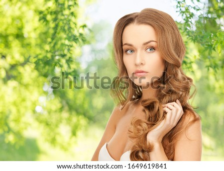 people, beauty and hair care concept - beautiful woman over green natural background