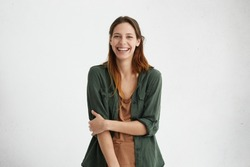 People, beauty and lifestyle concept. Shot of attractive sensual woman with wide smile dressed in green jacket and brown T-shirt smiling broadly being happy to meet her best friend. Joyful nice female