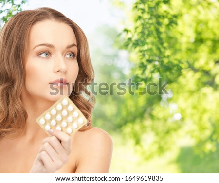 people, beauty and medicine care concept - beautiful woman with pills over green natural background