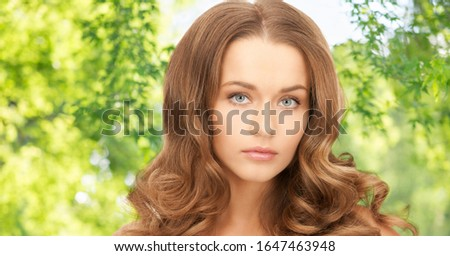 people, beauty and skin care concept - beautiful woman with curly hair over green natural background