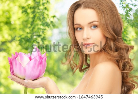 people, beauty and skin care concept - beautiful woman with pink lotus flower over green natural background